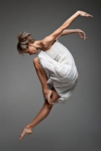beautiful young caucasian female dancer jumping over gray background